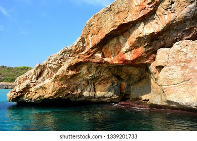 The view from the pleasure boat to the rocks and caves of the rocky shore and the blue clear water of the Mediterranean Sea near the resort town of Calas de Mallorca. Spanish island Mallorca