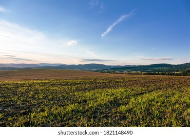 view of a plowed fertile field before sunset
