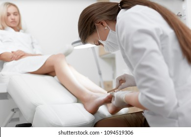 View of podiatrist doctor in white working at beauty salon, making polish procedure for foot with special equipment for blondie client. Young woman resting, caring about her health and foot.