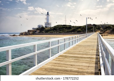 View of Point Lonsdale Lighthouse and jetty with seagulls in sky, Bellarine Peninsula, Victoria, Australia