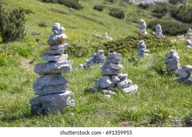 View point with white stone cairns on hiking trail Alta Via del Monte Baldo, ridge way in Garda Mountains, mountain edge