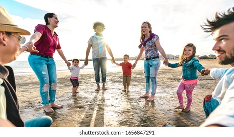 View point of young families dancing at beach on ring around the rosy style - Lifestyle joy concept with mixed race people having fun moment holding hands - Vivid backlight filter with sunshine halo