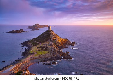View of Pointe de la Parata on the west coast of Corsica France Europe. A ruined Genoese tower sits on top of the rocky promontory overlooking the archipelago of the Sanguinaires on the colored sunset