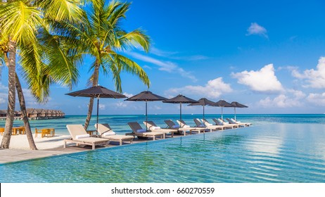 View from the pool to the beach with palm trees. Loungers and sun umbrella. Luxury vacation concept.