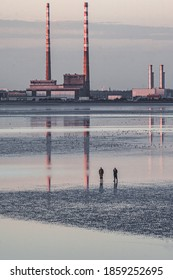 View of Poolbeg power station skyline of Dublin Ireland reflected in the water