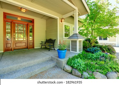 View of porch with entrance door, antique bench and flower bed