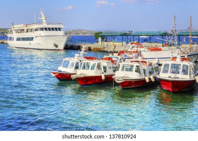 A view of the port of the beautiful Greek Island, Spetses. Four boats embarked, which are very characteristic of the island and a cruise ship on the background.