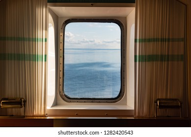 A view from the porthole window of a cruise ship, showing the sea and sunset