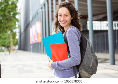 View of a Portrait of a young student with backpack going to school and holding notebook - Back to school