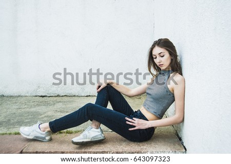 9d2634b08a7 view of portrait of young woman sitting outside in angle of gray wall. full  length