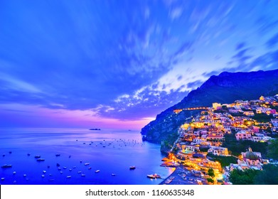 View of Positano village along Amalfi Coast in Italy at dusk.