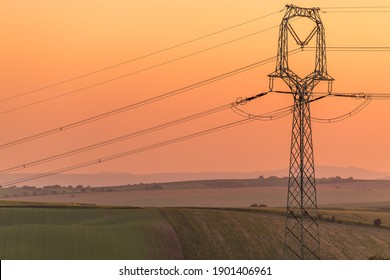 View of power line pylons during an orange sunset and the surrounding landscape.