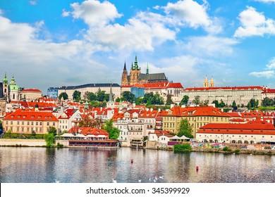 View of Prague Castle from waterfront- famous historic bridge that crosses the Vltava river in Prague, Czech Republic.