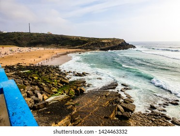 View of praia das maçãs in Portugal, with a bright blue wall in the foreground and waves and cliffs in the distance.