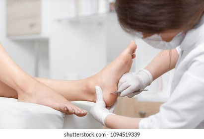 View of procedure of cleaning foot with iron tool in podiatrist cabinet. Profeesional doctor polish callus and corn on young feet skin of client. Concept of podiatry and medical.