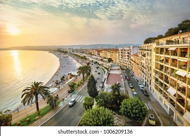 View of Promenade des Anglais in Nice with apartment houses and beach at sunset. France