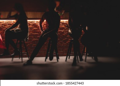 View of pub interior with people silhouettes drinking alcohol beverages and chatting at the bar counter, backlit illumination - Shutterstock ID 1855427443