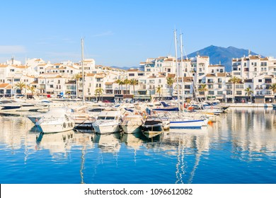View of Puerto Banus marina with boats and white houses in Marbella town at sunrise, Andalusia, Spain