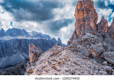 View from Puez-Geisler reserve in the Dolomite alps. Hiker with dogs standing on the rim, viewing the mountains.
