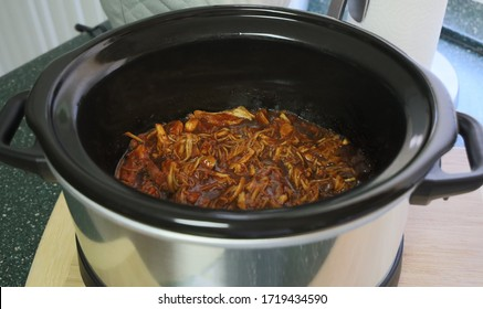 View of pulled chicken cooked in a crock pot.