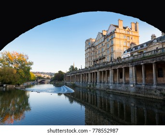 View of Pulteney Weir and Grand Parade from the River Avon under Great Pulteney Bridge in Bath, England, UK
