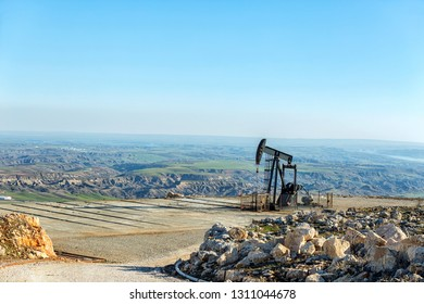 View of the pumpjack of the oil well in the oil field. Usually some natural gas is released along with the oil. A well that is designed to produce only gas may be termed a gas well.
