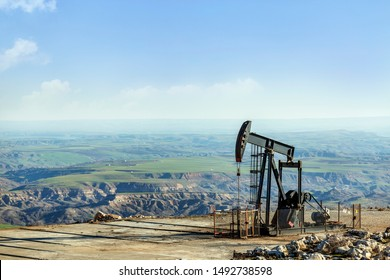 View of the pumpjack or piston pump in the oil well (oil field). Modern pumpjacks are powered by a prime mover. This is commonly an electric motor.