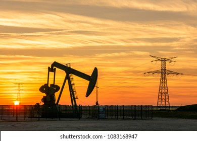 View of a pumpjack at sunset pumping oil out of a well in the center of France with the silhouettes of transmission towers supporting an overhead power line in the background against a red sky.