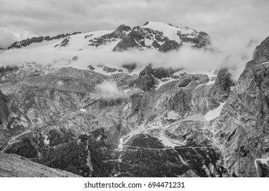 View of Punta Penia and Gran Vernel summits, mountains of Marmolada massif, wrapped in clouds, as seen from Alta Via 2 trail #601 down to Fedaia lake from Viel del Pan refuge, Dolomites, Italy