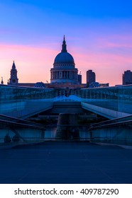 View of purple sunset at St Paul's Cathedral and the Millennium Bridge in London