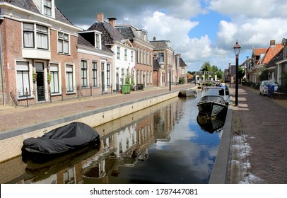 View of the quaint town of Kollum in Friesland in the Netherlands on a sunny summer's morning. View of the Trekvaart waterway, boats and waterfront houses.