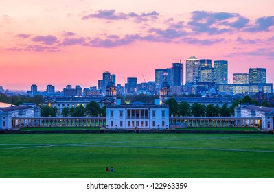 View of Queens House and Canary Wharf from Greenwich Park, London with a sunset sky