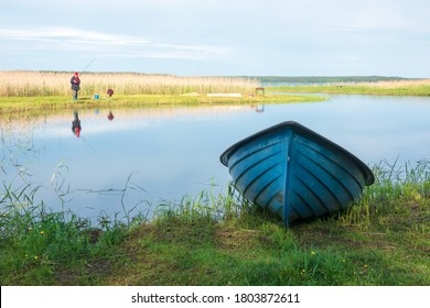 View of a quiet backwater by the lake. The figure of a fisherman is visible on the shore in the distance. In the foreground lies a blue rowboat.