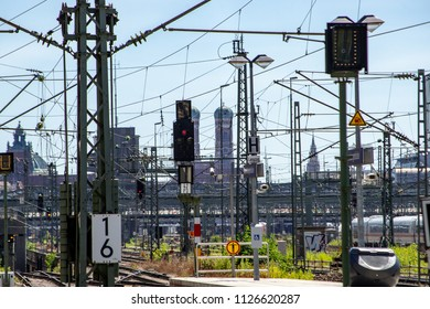 View of rail tracks and power lines leading to the Central Station in Munich, Germany with city landmarks in  the background