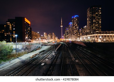 View of a rail yard and modern buildings in downtown at night, from the Bathurst Street Bridge in Toronto, Ontario.