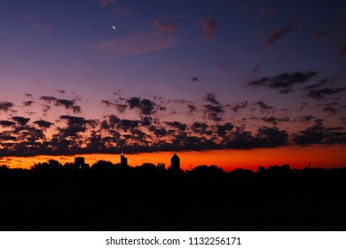 View of the Raleigh skyline with a crescent moon at twilight as seen from Dorothea Dix Park