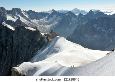 View of a range of high Alps and few mountaineers on a snow slope.