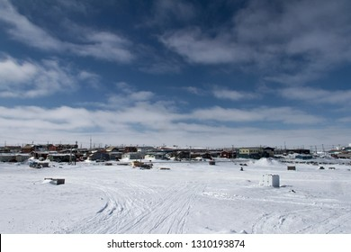 View of Rankin Inlet, a remote arctic community in Nunavut with blue skies and snow on the ground