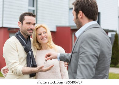 View of a Real estate agent delivers keys to young atractive couple