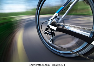 View of rear bicycle wheel with chain and cassette in motion