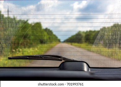 View of a rear glass of the car with the dirty  back glass with wiper, overlooking the road.
