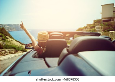 View from rear trunk area of convertible top automobile as driver with hat gestures with hand toward ocean