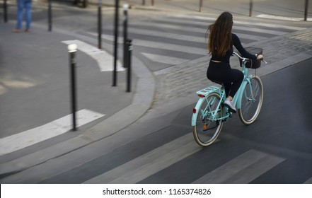 View from the rear of  woman cycling to work in a city. concept of eco-friendly transport. empty basket. girl with long brunette hair wear black dress