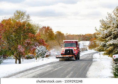 View of red truck with snowplow plowing suburban Midwestern street after first snowfall; some trees preserve their colorful fall leaves; Missouri
