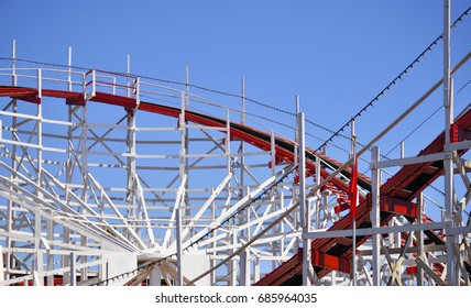 A view of an red and white wooden amusement park roller coaster