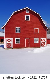 View of a red wooden barn under snow after a winter storm in New Jersey