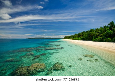 The view of the reef in beautiful turquoise tropical water by a white sand beach island covered in green lush on a sunny day with blue sky and silky white clouds.