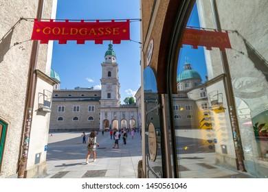 View of reflections in Goldgasse shop windows and Salzburg Cathedral in Residenzplatz, Salzburg, Austria, Europe 1-5-2019