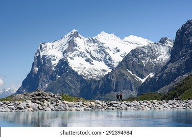 The view from the reservoir on the slopes of the Eiger, looking towards the Wetterhorn, showing walkers.