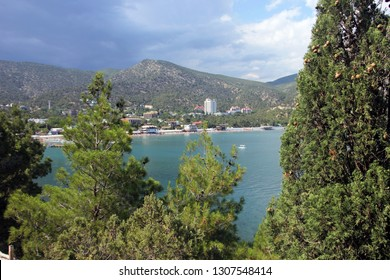 view of the resort coastal town at the foot of the green mountains through the green branches of pine and juniper